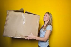 woman carrying a box while relocating to cut Pittsburgh moving expenses