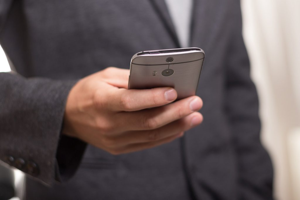 A person with a phone - evade a Pittsburgh moving scam by having in-house estimate.