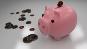 A pink piggy bank with coins next to it.