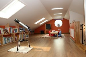Attic kids room with telescope, book shelf, table and small chairs