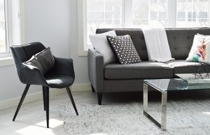 A chair, a sofa and a table on a rug next to the window