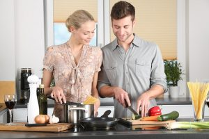 Man and woman in kitchen, cooking