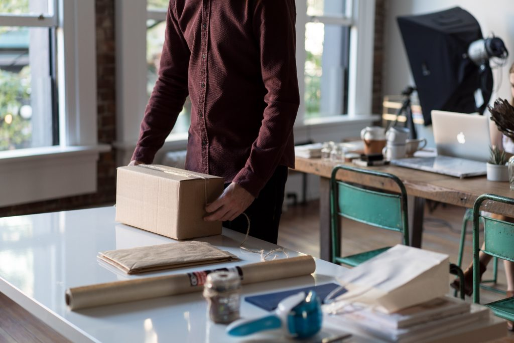 Man packing a box and planning to tip movers