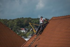 A man on the roof with tools