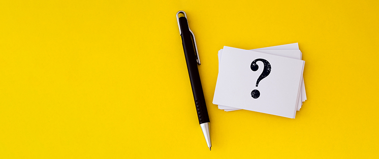 question mark and a pen on a yellow background