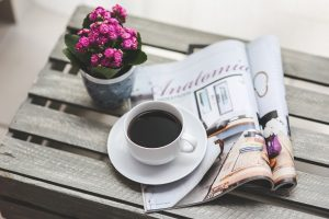 A magazine, a plan, and a cup of coffee on the table.
