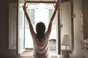 Woman with open arms in front of an open window