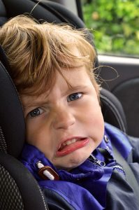 Boy is crying in a car seat