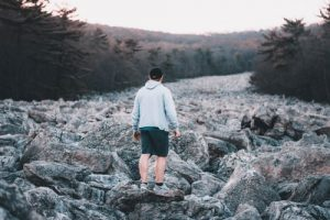 man in gray hoodie standing on gray rock